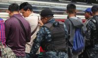 Agentes de la PNC hacen una revisión a pasajeros de un autobús. (Foto Prensa Libre: PNC).