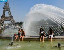 La gente combate la ola de calor refrescándose en las fuentes de Trocadero, con la Torre Eiffel al fondo. (Foto Prensa Libre: AFP Bertrand Guay).