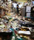 Un empleado trabaja en la caja registradora cerca de botellas rotas esparcidas en el piso, luego del sismo de magnitud 7.1 que afectó California. (Foto Prensa Libre AFP).