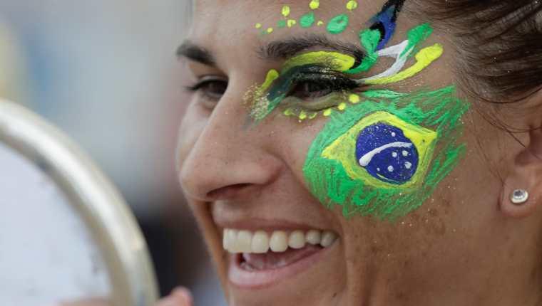 Una aficionada ríe tras recibir un maquillaje del artista colombiano Guillermo León Londoño este martes en el espacio Evolución es Conmebol en la playa de Copacabana en Río de Janeiro, Brasil (Foto Prensa Libre: EFE)