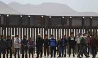 EL PASO, TX - MAY 17: A U.S. Border Patrol agent (R) walks past migrants being detained after crossing to the U.S. side of the U.S.-Mexico border barrier (BACKGROUND) on May 17, 2019 in El Paso, Texas. The location is an area where migrants frequently turn themselves in and ask for asylum after crossing the border. Approximately 1,000 migrants per day are being released by authorities in the El Paso sector of the U.S.-Mexico border amidst a surge in asylum seekers arriving at the Southern border.   Mario Tama/Getty Images/AFP