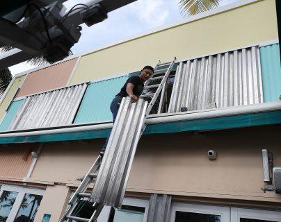 Miles de personas se preparan y protegen las ventanas y puertas para recibir la intensa lluvia. (Foto Prensa Libre: AFP)