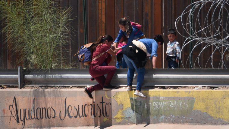 Una madre migrante junto con sus hijos brincan la barda fronteriza que separa a Estados Unido y México, cercano al puente internacional de Santa Fe, en Ciudad Juárez, en el estado de Chihuahua, México. (Foto Prensa Libre: EFE)
