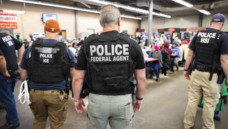 Agentes custodian a los migrantes que fueron detenidos en varios operativos en fabricas de Misisipi. (Foto Prensa Libre: EFE)