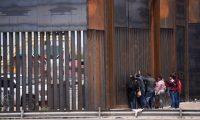 Migrantes centroamericanos se asoman por el muro fronterizo para entregarse a las autoridades estadounidenses. (Foto Prensa Libre EFE)