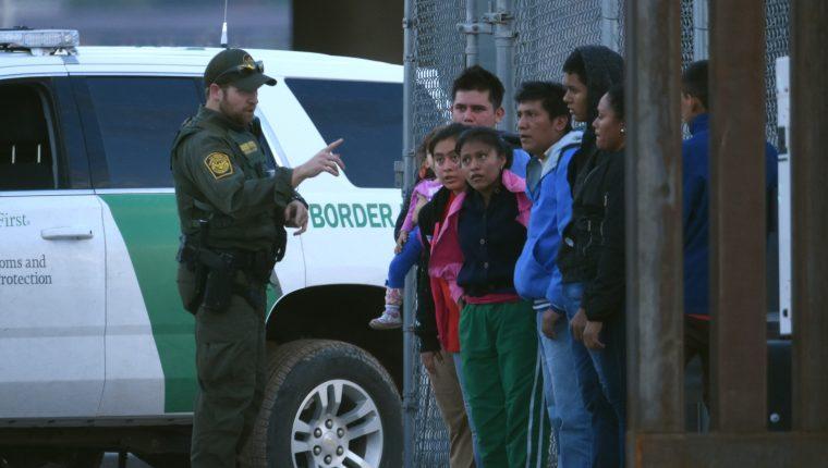 Un agente de la patrulla fronteriza estadounidense habla a un grupo de jóvenes migrantes centroamericanos tras ser detenidos en la orilla del Rio Bravo, en la fronteriza Ciudad Juárez. (Foto Prensa Libre: EFE)