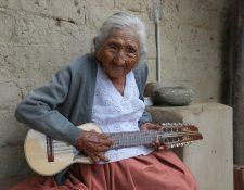 """En la fotografía, Julia Flores Qolque, más conocida en Bolivia cómo """"Mamá Julia"""", mientras toca su charango, en su casa de la localidad de Sacaba, a 18 kilómetros de la ciudad de Cochabamba (Bolivia). Mamá Julia, considerada la más longeva de su país, murió este sábado en la mañana a dos meses de cumplir los 119 años de vida. (Foto Prensa Libre: EFE)"""