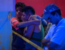 Familiares de las víctimas aguardan al exterior del local donde al menos 23 personas murieron. (Foto Prensa Libre: EFE)
