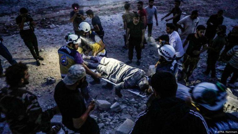 """Los """"cascos blancos"""" evacúan a una persona rescatada de un edificio derrumbado tras los bombardeos en la ciudad de Kfar Ruma, castigada por los bombardeos de este viernes."""