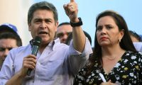 """Handout picture released by the Honduran presidency press office showing Honduran President Juan Orlando Hernandez -who was accused of allegedly being linked to drug trafficking- next to his wife Ana Garcia while addressing supporters, in Tegucigalpa on August 6, 2019. - Hundreds of people took to the streets today demanding Hernandez's resignation. (Photo by HO / AFP) / RESTRICTED TO EDITORIAL USE - MANDATORY CREDIT """"AFP PHOTO /  HONDURAS PRESIDENCY PRESS OFFICE"""" - NO MARKETING - NO ADVERTISING CAMPAIGNS - DISTRIBUTED AS A SERVICE TO CLIENTS"""