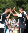 Paulo Dybala celebra con el mediocampista  Miralem Pjanic después de anotar en el partido amistoso de la Juventus a contra la Juventus B en Villar Perosa. (Foto Prensa Libre: AFP).
