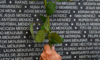 A woman puts a flower near the name a relative at the monument to the people who disappeared during the civil war commemorating the International Day of the Disappeared, at Cuscatlan Park in San Salvador, on August 30, 2019. - About 8000 people went missing during El Salvador's 1979-1992 civil war between his leftist guerrillas and US-backed rightwing governments (Photo by Oscar Rivera / AFP)
