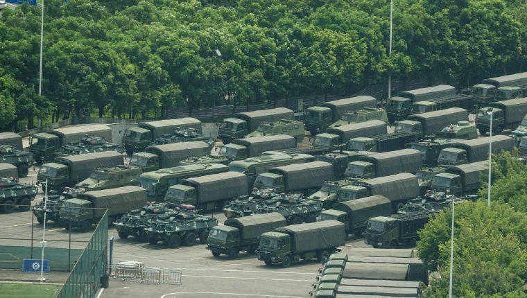 Camiones y vehículos blindados se ven fuera del estadio de la Bahía de Shenzhen en Shenzhen, en la frontera con Hong Kong en la provincia meridional china de Guangdong. (Foto Prensa Libre: AFP).