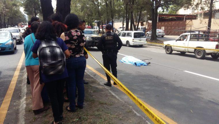 Curiosos observan el lugar donde murió arrollada una estudiante en el Anillo Periférico. (Foto Prensa Libre: Nimsi Rosales).