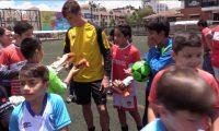 Nicholas Hagen le entrega sus guantes al pequeño Javier Gómez. (Foto Prensa Libre: Luis López)
