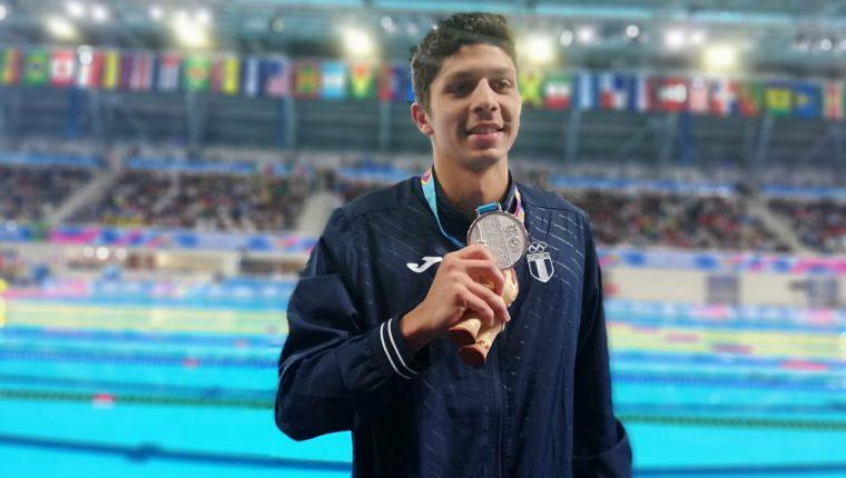 El nadador guatemalteco Luis Carlos Martínez posa con la medalla de plata que conquistó en Lima 2019. (Foto Prensa Libre: Carlos Vicente).