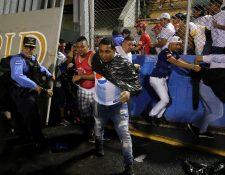 Aficionados ingresan al campo y se protegen de los gases lacrimógenos lanzados por las autoridades, debido a los disturbios a las afueras del Estadio Nacional por la cancelación del clásico entre Olimpia y Motagua. (Foto Prensa Libre: EFE)