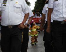 Algunos niños vestidos de bomberos acompañan al pelotón de paramédicos. Fotografía Prensa Libre: Noé Medina.
