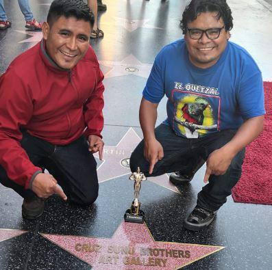 Los hermanos Lorenzo y Pedro Cruz Sunú colocan simbólicamente una estrella en el Paseo de la Fama en Hollywood. (Foto Prensa Libre: Cortesía).