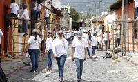 Un grupo de estudiantes de Arquitectura de la UMG participa en la campaña de rescate de los colores antigüeños en el barrio de la Escuela de Cristo de Antigua Guatemala. (Foto Prensa Libre: Julio Sicán)