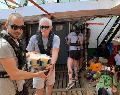 El actor estadounidense Richard Gere -derecha- entrega víveres en el barco que alberga a migrantes. (Foto Prensa Libre: EFE).