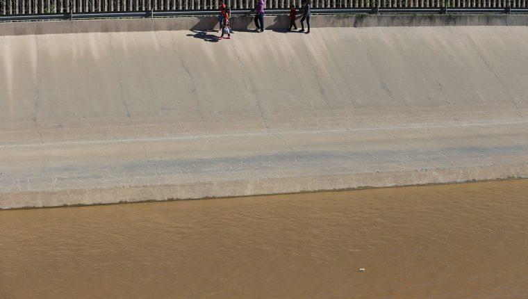 Migrantes centroamericanos intentan adentrarse en territorio estadounidense luego de haber sorteado las aguas del río Bravo, en el punto fronterizo de Ciudad Juárez, México. (Foto Prensa Libre: EFE)