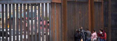 Migrantes centroamericanos se asoman en por el muro fronterizo, para entregarse a las autoridades migratoria estadounidenses, en el tramo de Puente Nuevo, en Ciudad Juárez (México). (Foto Prensa Libre: EFE)