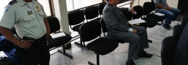 Un agente de la Policía Nacional Civil permanece al lado del viceministro de Gobernación, Remberto Ruiz, durante la audiencia. (Foto Prensa Libre: Kenneth Monzón)