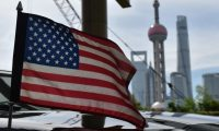 (FILES) In this file photo taken on July 30, 2019 a US flag flies on a US consulate car with the backdrop of buildings in the Lujiazui financial district, outside a hotel where US trade negotiators are staying in Shanghai. - US tariffs on China won't fix the trade deficit, and neither will weakening the US dollar through interest rate cuts, International Monetary Fund economists said August 21, 2019. In unusually-blunt language, the blog post seemed targeted straight at President Donald Trump who has loudly and constantly demanded the Federal Reserve cut interest rates to weaken the US dollar and juice the economy, while imposing round after round of tariffs on China to reduce the deficit he describes as theft. (Photo by GREG BAKER / AFP)