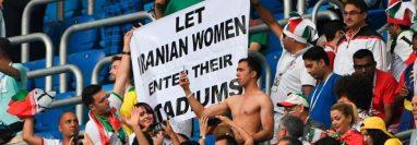 """En Irán, las mujeres no pueden entrar a los estadios de fútbol desde la revolución islámica, en 1979. En la foto, varias personas sostienen una pancarta que dice """"permitamos que las mujeres iraníes entren en sus estadios"""". GETTY IMAGES"""