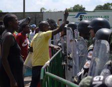 Migrantes de origen africano protestan frente a miembros de la Guardia Nacional de México. Los migrantes, que se manifiestan desde hace varios días, acusan a las autoridades de tenerlos varados en Chiapas. (Foto Prensa Libre: EFE)