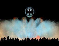 """Centenares de personas observan el espectáculo de la Fuente Mágica de Montjuic mientras en la cúpula del Museu Nacional d'Art de Catalunya (MNAC), en Barcelona, se observa la """"Batiseñal"""", el símbolo de Batman, que se proyectará en una catorcena de ciudades de todo el mundo por el 80 aniversario del Caballero Oscuro. Foto Prensa Libre: EFE"""
