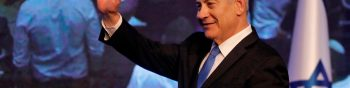 """Israeli Prime Minister Benjamin Netanyahu waves as he addresses supporters at his Likud party's electoral campaign headquarters early on September 18, 2019. - Israeli Prime Minister Benjamin Netanyahu said he was waiting for results in the country's general election, but that he was prepared for negotiations to form a """"strong Zionist government."""" He spoke as exit polls showed a tight race between his right-wing Likud and ex-military chief Benny Gantz's centrist Blue and White alliance. (Photo by Menahem KAHANA / AFP)"""