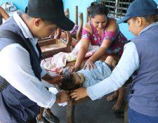 Los integrantes del Comusan comprueban el peso y talla de los menores que visitados en sus casas de Puerto San José, Escuintla. (Foto Prensa Libre: Carlos Paredes)
