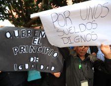 Trabajadores de gobernaciones departamentales muestran pancartas para exigir aumento. (Foto Prensa Libre: Carlos Hernández).