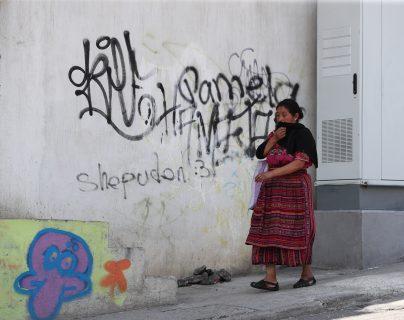 Una vecina camina frente a un grafitti pintado en una de las paredes de un inmueble del bulevar principal de Prados de Villa Hermosa. (Foto Prensa Libre: Érick Ávila)
