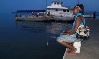La vecina Claudia Flores observa la llegada de pocas embarcaciones en el muelle de Livingston, donde expresa que el Estado de Sitio ha representado baja en turismo en la localidad.