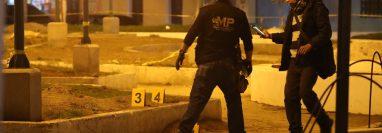 Dos investigadores del Ministerio Público marcan el lugar donde localizaron los cascabillos. (Foto Prensa Libre: Mynor Toc)