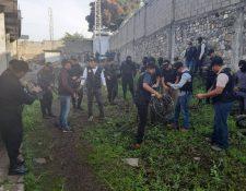 Investigadores enrollan el cable decomisado en los alrededores de la cárcel de El Boquerón, en Cuilapa, Santa Rosa. (Foto Prensa Libre: PNC).