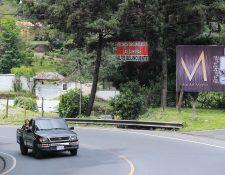 """Un kilómetro antes de llegar al centro urbano de San Juan Sacatepéquez un rótulo colgado en un poste de energía eléctrica, en la ruta principal,  advierte de """"vigilancia a delincuentes"""". (Foto Prensa Libre: Juan Diego González)"""