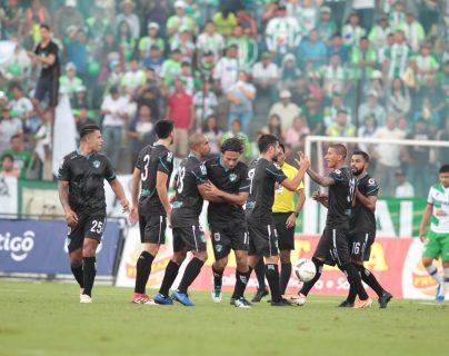 Los cremas festejan el triunfo contra Antigua. Atrás el árbitro Wálter López observa. (Foto Prensa Libre: Norvin Méndoza)