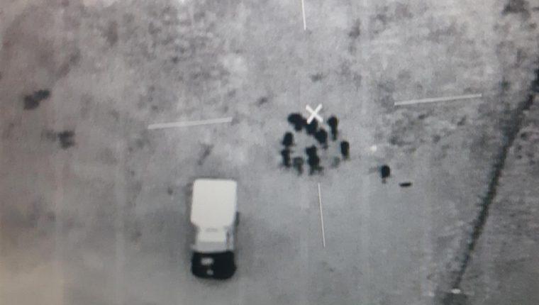 Foto satelital difundida por el Ejército guatemalteco donde se ve a personas llevando carga a un vehículo cerca de la escuela donde los soldados estaban retenidos.