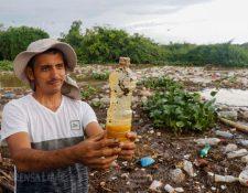 Poblador muestra una botella de aceite que supuestamente llegó  desde la cabecera de Retalhuleu hasta la reserva Manchón Guamuchal. (Foto Prensa Libre: Rolando Miranda)