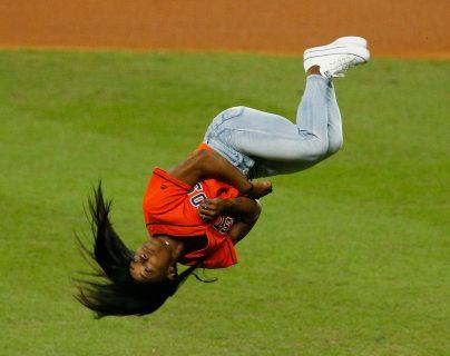 Simon Biles demostró un poco de su talento al hacer un salto mortal antes de hacer un saque de honor en la Serie Mundial. (Foto Prensa Libre: AFP)