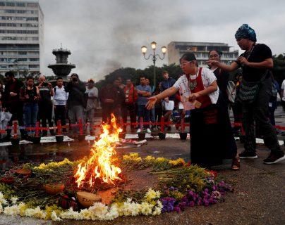 Una niña aviva el fuego durante una ceremonia para reinstalar el altar en memoria de las 41 niñas y adolescentes que murieron quemadas en el Hogar Seguro. (Foto Prensa Libre: EFE)