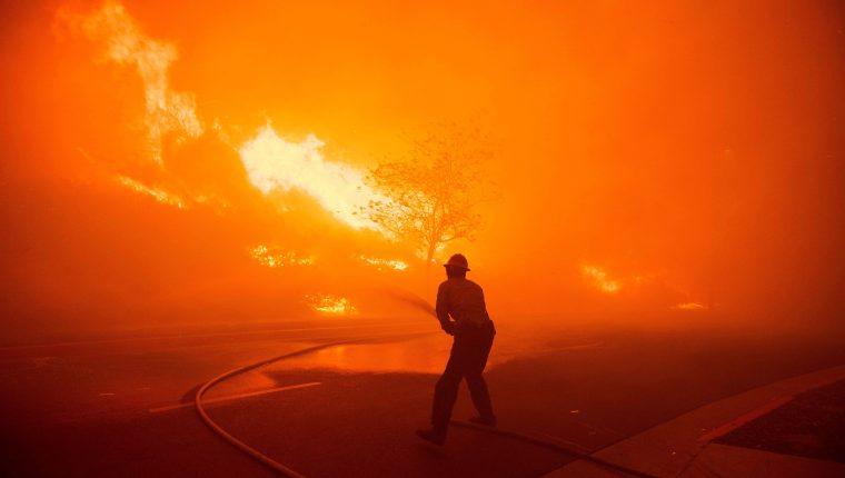 Un bombero de Texas sofoca las llamas en el incendio de Saddlebridge en Silmar, California. (Foto Prensa Libre: EFE)