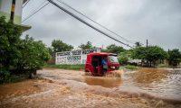 """MEX5841. TEHUANTEPEC (MÉXICO), 16/10/2019.- Habitantes del Istmo de Tehuantepec transitan por una calle inundada mientras llueve este miércoles, en el estado de Oaxaca (México). Un ciclón que se formó en las últimas horas en el Pacífico tocará tierra en el sur de México en las próximas horas como depresión tropical, propiciando fuertes lluvias, informó este miércoles el Servicio Meteorológico Nacional (SMN). """"El ciclón tropical potencial Diecisiete-E se localiza al sur de las costas de Oaxaca. Se pronostica que en las próximas horas se intensifique a depresión tropical"""", detalló el organismo en un boletín. EFE/ Luis Villalobos"""