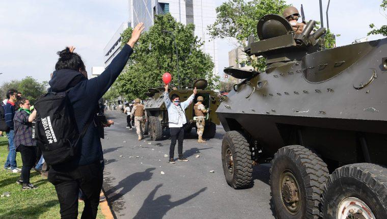 Los manifestantes se paran frente a vehículos militares en Santiago, el 19 de octubre de 2019. (Foto Prensa Libre: AFP).