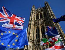 Las banderas pertenecientes a activistas anti-Brexit y pro-Brexit vuelan fuera de las Casas del Parlamento en Londres cuando los parlamentarios comienzan a debatir la segunda lectura del proyecto de ley de Acuerdo de Retirada. (Foto Prensa Libre AFP)
