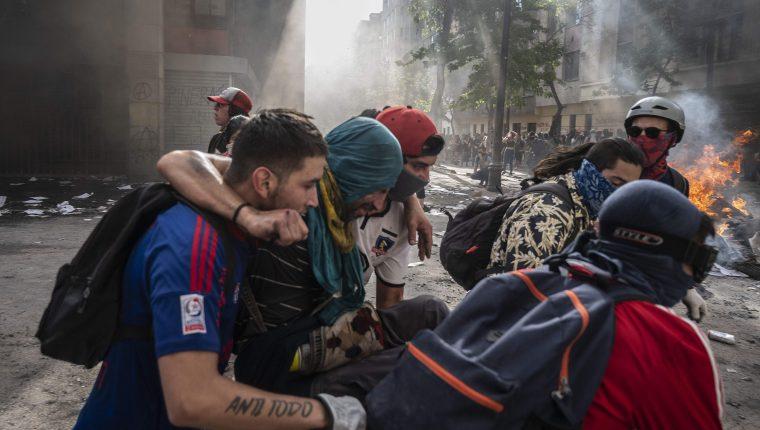 En la Plaza Italia, manifestantes ayudan a otro manifestante en apuros durante el quinto día consecutivo de protestas que estalló por un alza ahora suspendida en los precios de los boletos del metro. (Foto Prensa Libre: AFP)